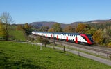 An LD double-decker on a sunny day in Zeihen on the Bözberg line between Basel and Brugg. On the left-hand side of the train there is meadow with a small footpath and to the right there is an autumnal forest.