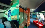 "IC2000: Interior view of the Ticki Park family coach. To the right of the picture, there is a red wooden boat with a holding rail and seats. The passage to the slide is the focus of the image. The walls are designed to fit the ""jungle"" theme."