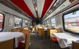 ICN: Interior view of the restaurant car. To the left and right of the picture there are corner tables for two and semi-circular tables for five. The chairs are wooden with a comfortable red seat cushion. The tables have white tablecloths.