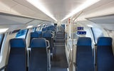 2nd class interior – there are compartments to seat four on both sides of the aisle. The seat cushions are dark blue. On the right-hand side there are stairs to the lower deck between the compartments.
